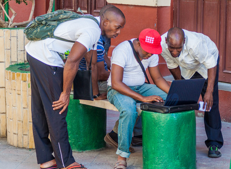 GUANTANAMO, CUBA - FEB 3, 2016: Local people use internet at the pedestrian zone of Aguilera street in Guantanamo. This is one of the few Wi-Fi access points in Cuba. Editorial