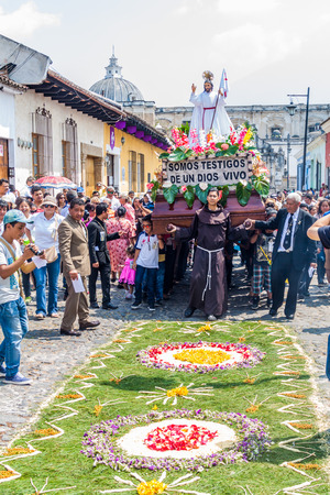 ANTIGUA, GUATEMALA - MARCH 27, 2016: The procession is crossing one of the many decorated carrpets on Easter Sunday in Antigua Guatemala city.