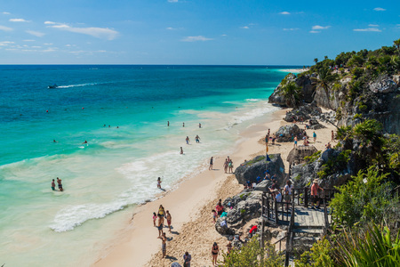 TULUM, MEXIO - FEB 29, 2016: Tourists at the beach under the ruins of the ancient Maya city Tulum, Mexico Editorial