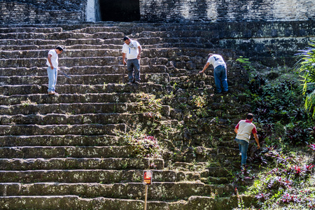 TIKAL, GUATEMALA - MARCH 14, 2016: Workers maintain the ruins of Complex P at the archaeological site Tikal, Guatemala Editorial
