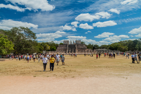 yucatan: CHICHEN ITZA, MEXICO - FEB 26, 2016: Crowds of tourists visit the archeological site Chichen Itza. The Temple of the Warriors in the background.