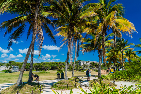 TULUM, MEXIO - FEB 29, 2016: Tourists visit the ruins of the ancient Maya city Tulum, Mexico