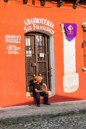 local 27: ANTIGUA, GUATEMALA - MARCH 27, 2016: Local man sits at the doorway of a colorful colonial house in Antigua, Guatemala