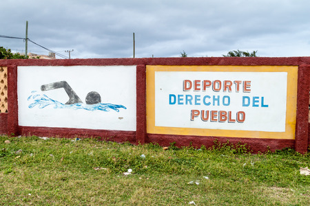 communism: GIBARA,  CUBA - JAN 29, 2016: Mural on a wall of the swimming pool in Gibara village. It says: Sport, the right of the peoples.