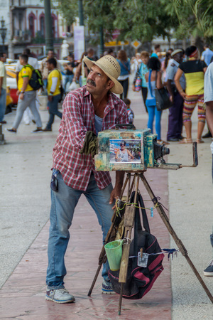HAVANA, CUBA - FEB 20, 2016: Street photographer using a vintage camera in Parque Central, the center of Havana.