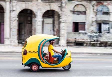 HAVANA, CUBA - FEB 22, 2016: Coco taxi rides along the famous seaside drive Malecon in Havana