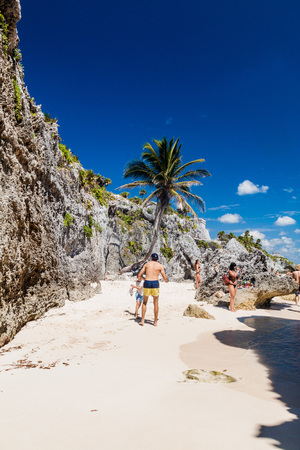yucatan: TULUM, MEXIO - FEB 29, 2016: Tourists at the beach under the ruins of the ancient Maya city Tulum, Mexico Editorial