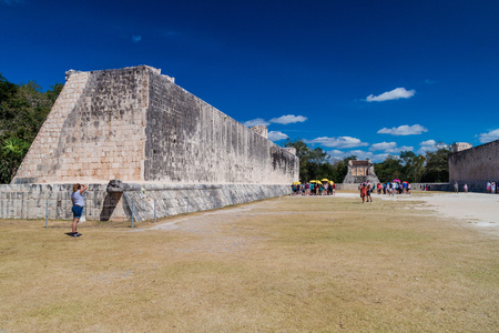 CHICHEN ITZA, MEXICO - FEB 26, 2016: Crowds of tourists visit The great ball game court at the archeological site Chichen Itza.