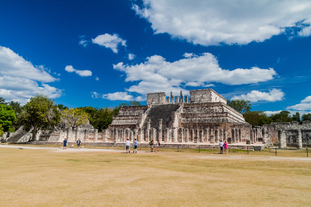 CHICHEN ITZA, MEXICO - FEB 26, 2016: Crowds of tourists visit the archeological site Chichen Itza. The Temple of the Warriors in the background.