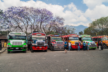 ANTIGUA, GUATEMALA - MARCH 28, 2016: Colourful chicken buses, former US school buses, are lined up at the main bus terminal in Antigua Guatemala city.