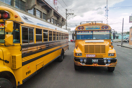 QUETZALTENANGO, GUATEMALA  - MARCH 21, 2016: Colourful chicken buses, former US school buses, ride in Quetzaltenango city.