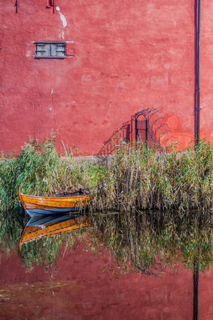 Walls of Malmo Castle and a small boat reflecting in a moat, Sweden