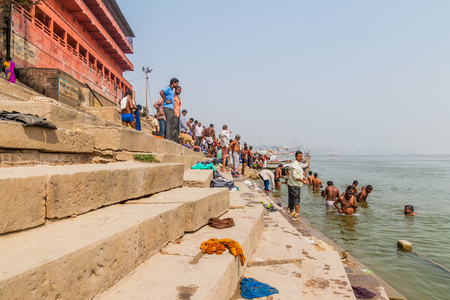 VARANASI, INDIA - OCTOBER 25, 2016: Local people wash themself in sacred water of Ganges rover at a Ghat (riverfront steps) in Varanasi, India