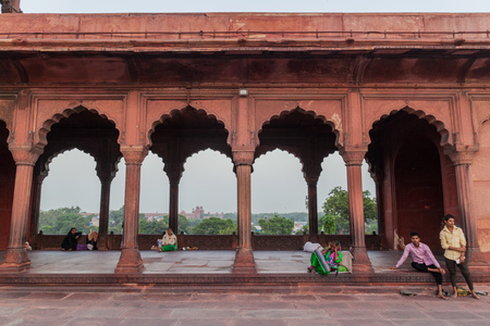 colonade: DELHI, INDIA - OCTOBER 22, 2016: Colonade around the courtyard of Jama Masjid mosque in the center of Delhi, India. Red Fort in the background.