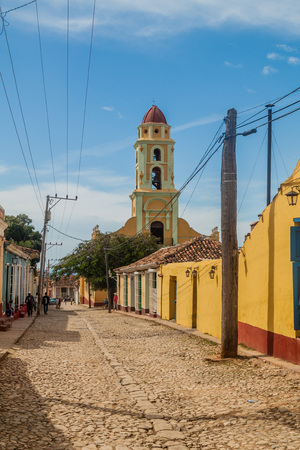TRINIDAD, CUBA - FEB 8, 2016: View of a cobbled street in the center of Trinidad, Cuba. Bell tower of Museo Nacional de la Lucha Contra Bandidos in the background.