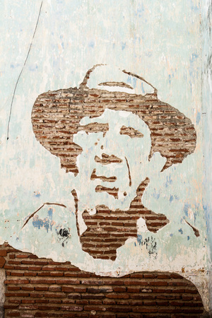 Portrait of cuban heroe Camilo Cienfuegos at an old wall in Camaguey, Cuba Editorial