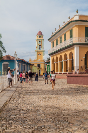 TRINIDAD, CUBA - FEB 8, 2016: Tourists walk on a cobbled street in the center of Trinidad, Cuba. Bell tower of Museo Nacional de la Lucha Contra Bandidos in the background. Redactioneel