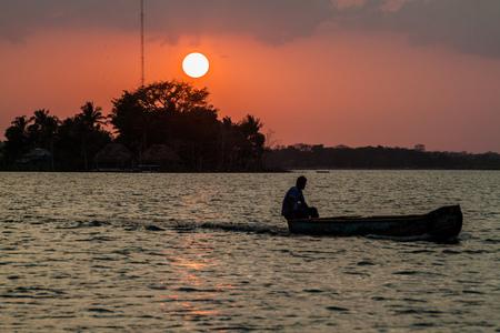 Sunset behind Santa Barbara islet with a boat crossing Peten Itza lake near Flores city, Guatemala Stock Photo
