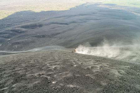 Tourist is volcano boarding from Cerro Negro volcano, Nicaragua Reklamní fotografie