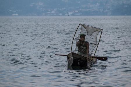 SAN MARCOS LA LAGUNA, GUATEMALA - MARCH 24, 2016: Fisherman on traditional wooden boats on Atitlan lake near San Marcos La Laguna village. Editorial