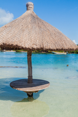 Table and a parasol in a water at Caye Caulker island, Belize Stock Photo