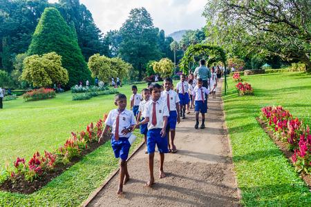 KANDY, SRI LANKA - JULY 18, 2016: Group o students visit beautiful Peradeniya Royal Botanical Gardens near Kandy, Sri Lanka