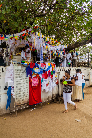 KANDY, SRI LANKA - JULY 19, 2016: White clothed buddhist pilgrims visit Wel Bodiya with Bodhi tree during Poya (Full Moon) holiday in Kandy, Sri Lanka