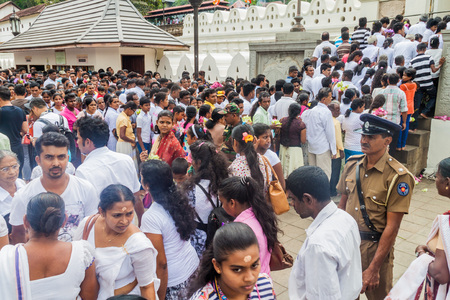 KANDY, SRI LANKA - JULY 19, 2016: White clothed Buddhist devotees wait in a queue at the entrance to the Temple of the Sacred Tooth Relic during Poya (Full Moon) holiday.