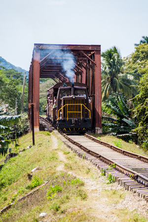 GUACHINANGO, CUBA - FEB 9, 2016: Local train crossing a bridge over Ay river in Valle de los Ingenios valley near Trinidad, Cuba Editorial
