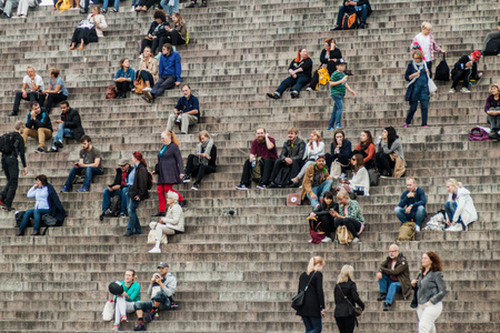 HELSINKI, FINLAND - AUGUST 25, 2016: People sit on stairs on the Senate Square in front of the Finnish Evangelical Lutheran cathedral. Editorial