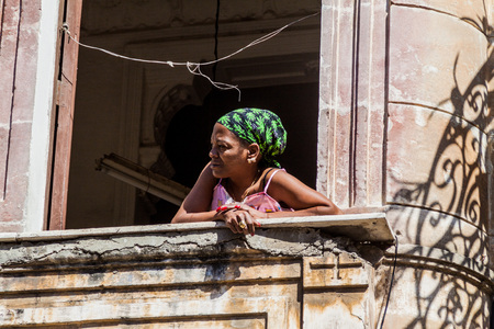 HAVANA, CUBA - FEB 22, 2016: Local woman watches out of the window in a dilapidated house in Havana Centro neighborhood, Havana, Cuba Editorial