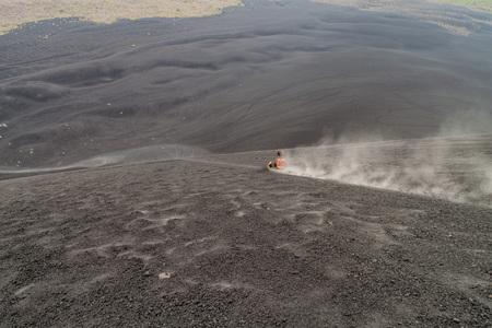 CERRO NEGRO, NICARAGUA - APRIL 26, 2016: Tourist is volcano boarding from Cerro Negro volcano, Nicaragua Redakční