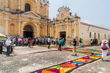 ANTIGUA, GUATEMALA - MARCH 27, 2016: People walk along decorative Easter carpets in front of San Pedro Apostol church in Antigua Guatemala town, Guatemala. Editorial