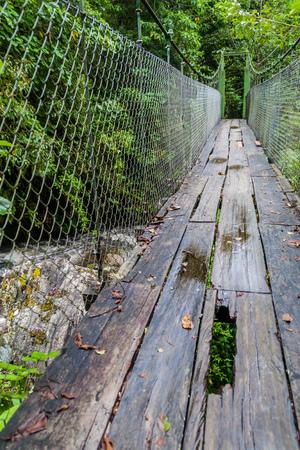 Suspension bridge at the hiking trail Sendero Los Quetzales in National Park Volcan Baru during rainy season, Panama.
