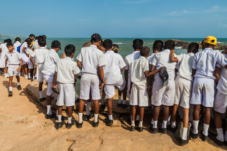 GALLE, SRI LANKA - JULY 12, 2016: Children in school uniforms watch a sea from fortification walls of Galle. Editorial
