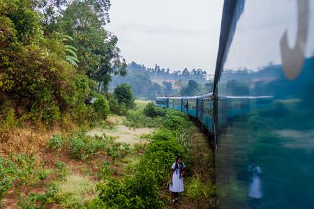 ELLA, SRI LANKA - JULY 15, 2016: Girl in a school uniform walk along railway tracks near Ella, Sri Lanka