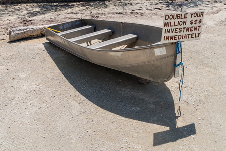 CAYE CAULKER, BELIZE - MARCH 2, 2016: Small boat with a sign double your investment at Caye Caulker island, Belize