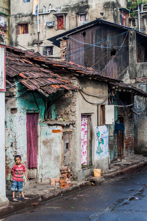 KOLKATA, INDIA - OCTOBER 30, 2016: Small boy by dilapidated houses in the center of Kolkata, India