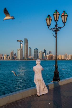 ABU DHABI, UAE - MARCH 7, 2017: Local man photographs the skyline of Abu Dhabi from the Marina Breakwater, United Arab Emirates