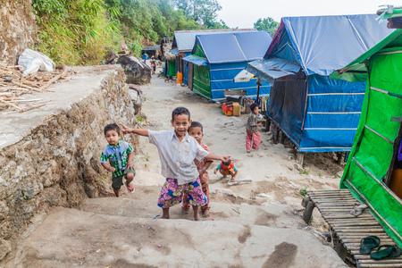MT KYAIKTIYO, MYANMAR - DECEMBER 11, 2016: Local children and snack stalls at the hiking trail to Mt Kyaiktiyo (Golden Rock). Stock Photo - 115418841