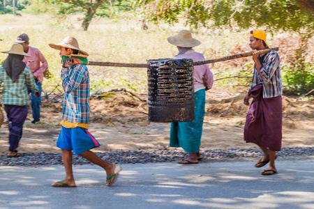 BAGAN, MYANMAR - DECEMBER 6, 2016: Local road building workers carrying a barrel of tar in Bagan, Myanmar Редакционное