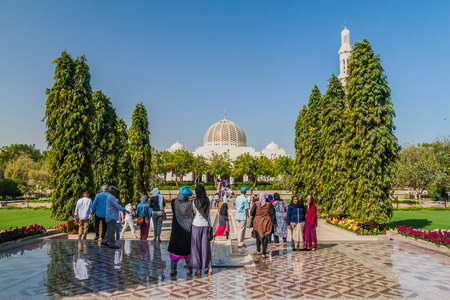 MUSCAT, OMAN - FEBRUARY 22, 2017: Visitors in a park of Sultan Qaboos Grand Mosque in Muscat, Oman
