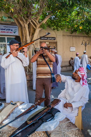 NIZWA, OMAN - MARCH 3, 2017: Rifle seller with his customers at the Souq in Nizwa, Oman Editorial