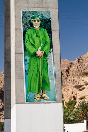 TIWI, OMAN - MARCH 4, 2017: Portrait of Sultan Qaboos on a pillar of a highway bridge over Wadi Tiwi, Oman