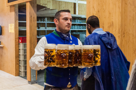 MUNICH, GERMANY - SEPTEMBER 17, 2016: Waiter carrying many beer glasses at the Oktoberfest in Munich Sajtókép
