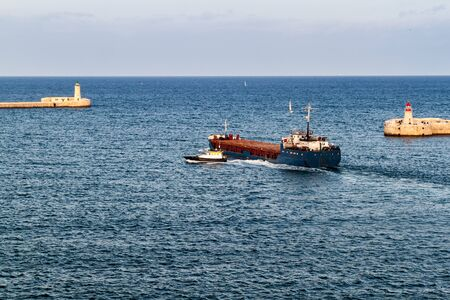 Cargo ship at the entrance to Grand Harbour in Malta Zdjęcie Seryjne