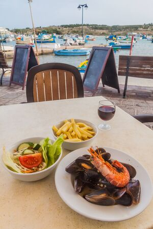 Sea food dish with fries and salad in a retaurant in the harbor of Marsaxlokk town, Malta