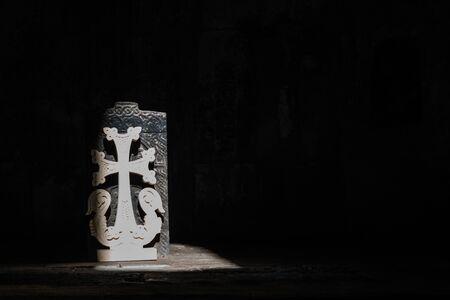 Stone cross illuminated by a beam of light in Sanahin monastery in Armenia Reklamní fotografie
