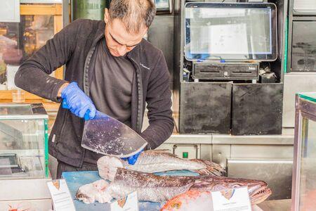 MADRID, SPAIN - OCTOBER 21, 2017: Seller is cutting a fish in Mercado de San Miguel market in Madrid. Stock fotó
