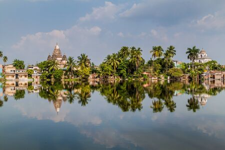 Shiva temple and Dol Mandir temple reflecting in a pond in Puthia village, Bangladesh